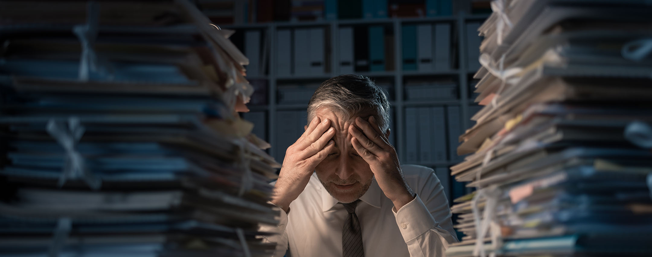 gentleman with his hands on his head sitting in front of two stacks of paper