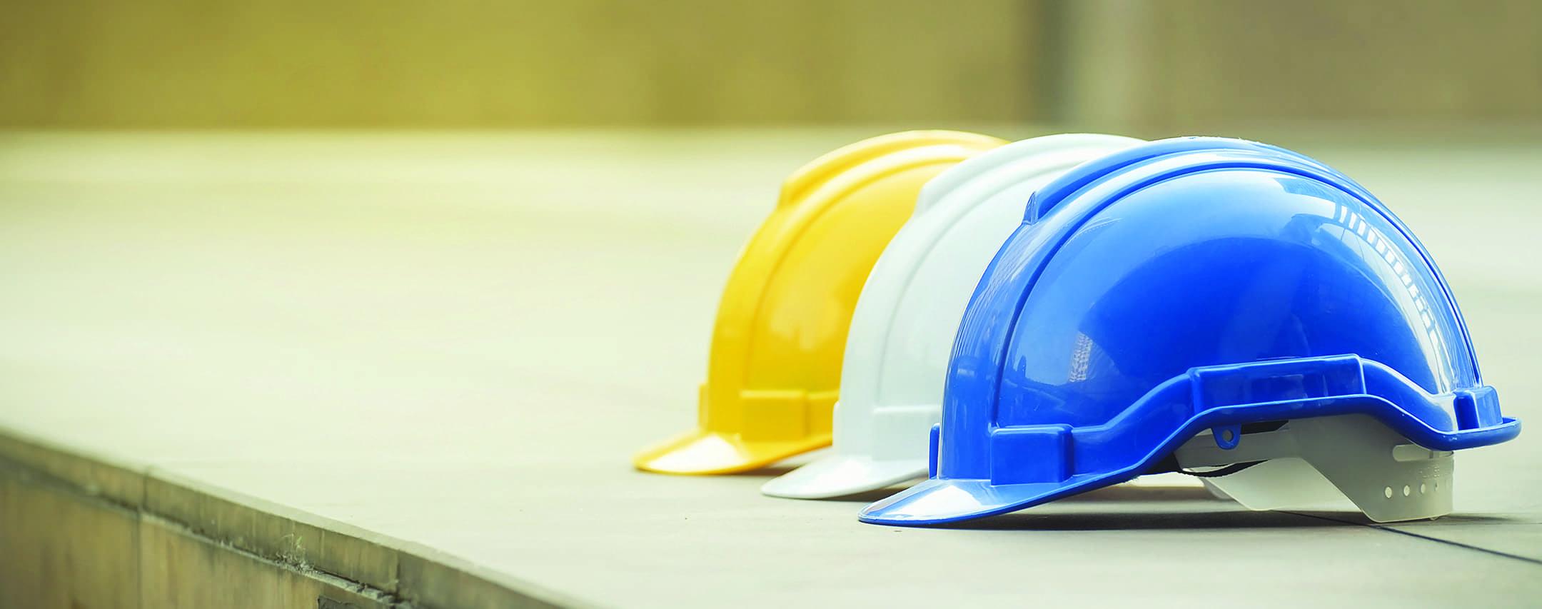 three hard construction hats lined up